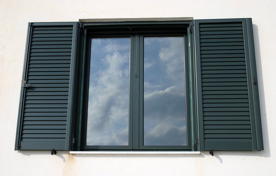 glass window with green shutters